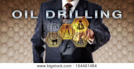Male industrial manager in blue business suit touching OIL DRILLING on a virtual interactive control screen. Petroleum industry metaphor. Drill bit symbol and engineer icon are highlighted in yellow.