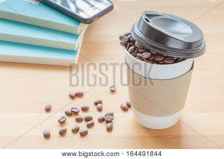 A paper cup of full roasted aroma coffee beans and some fallen on wooden board with blurred background, business concept.