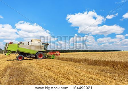 Combine harvester on a wheat field with blue sky.
