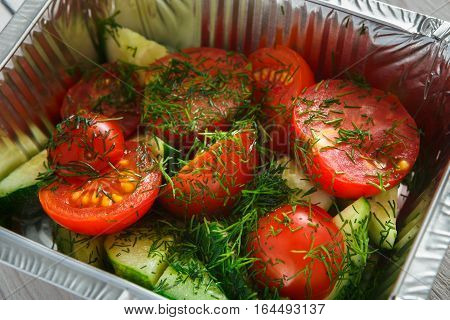 Healthy eating concept. Lunch foil box, take away organic food. Weight loss diet. Fresh vegetable salad from peppers, tomatoes and cucumbers, closeup