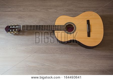 Guitar on wooden background fretboard, stringed musical instrument close-up