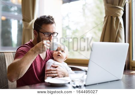 Young handsome man with notebook in cafe sitting at the table drinking coffee, holding his son in his lap