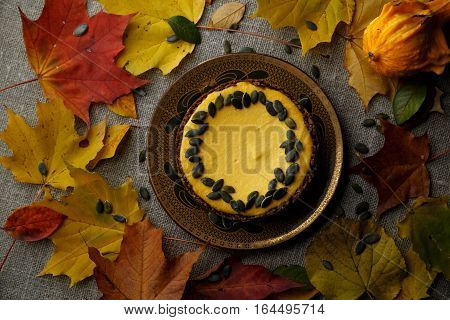 Delicious pumkin cake with leaves on background