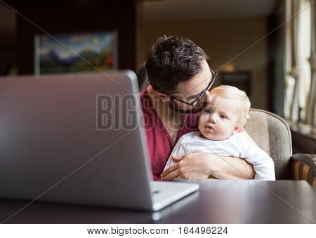 Young handsome man with notebook in cafe sitting at the table holding his son in his lap, kissing him on head