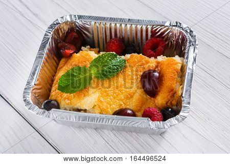 Healthy dessert. Sweet baked rice pudding with raspberry closeup in foil delivery box on white wood. Vegetarian diet. Fresh prepared food take away, natural organic meals