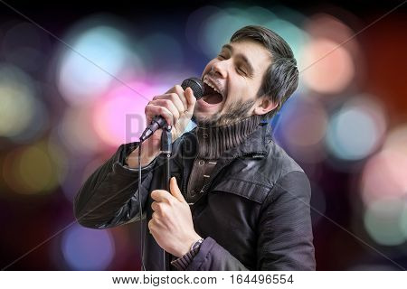 Karaoke Concept. Young Man Holds Microphone And Singing A Song O