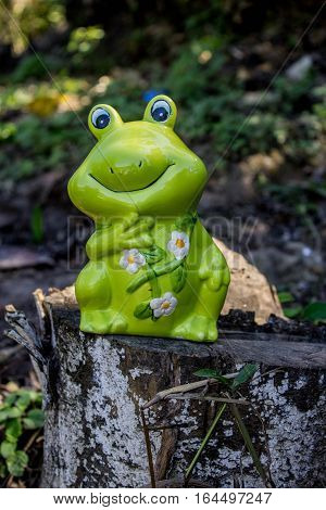 Green ceramic frog on a cut log