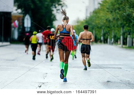 back young woman runner running in city marathon compression socks