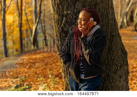 Woman talking by phone in the autumn park at sunset and smiling. Girl standing near tree and looking at the yellow leaves. Beautiful autamn park