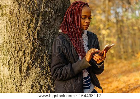 Woman standing near tree in the autumn park at sunset. Girl searching something in her phone. Beautiful autamn park