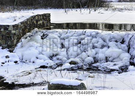Small spillway frozen into tufts of icicles