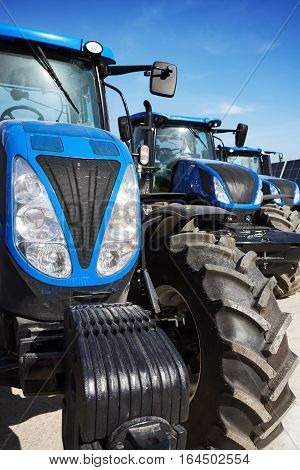 Many modern tractors, agricultural machines, cultivation of the soil on the farm, tractors against the sky, tractors standing in a row
