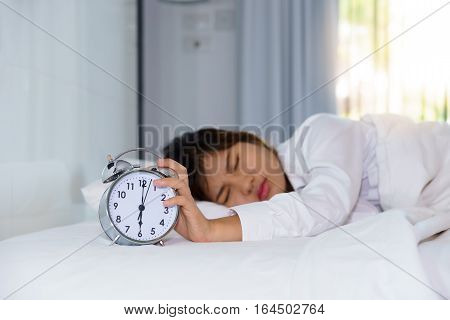 Sleepy young woman stretching hand to trying kill alarm clock in the morning. early wake up.