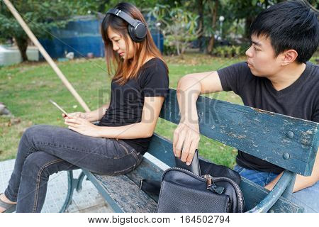 Thief trying to steal the wallet in the bag and look at woman while woman using mobile phone and listening to music on sofa in the park.