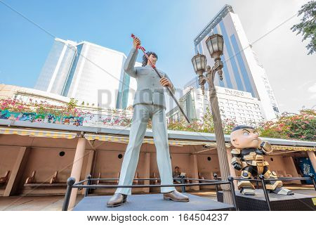 Hong Kong, China - December 5, 2016: Shau Sing Chai and Hero Wah, statues of famous characters, in Hong Kong Avenue of Comic Stars, Kowloon Park. Urban skyline and building background of Tsim Sha.