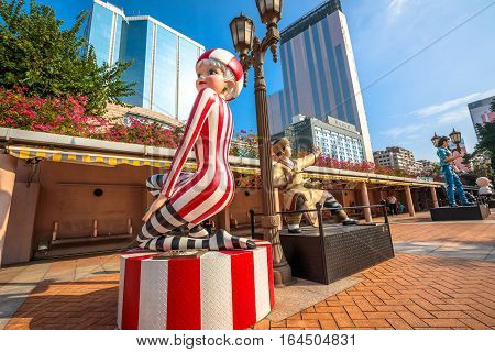 Hong Kong, China - December 5, 2016: Miss 13 Dots, Guo Jing and Wang Xiao Hu, statues of famous characters, in Hong Kong Avenue of Comic Stars, Kowloon Park. Urban skyline of Tsim Sha Tsui District.