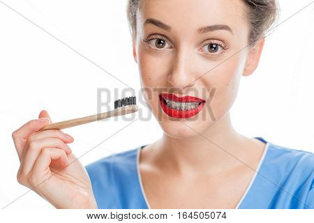 Portrait of confused woman with tooth braces holding a toothbrush on the white background. Woman worried about tooth cleaning with braces