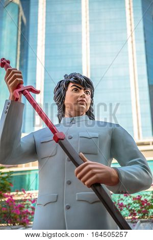 Hong Kong, China - December 5, 2016: close up of Hero Wah, statue of famous characters, in Hong Kong Avenue of Comic Stars, Kowloon Park. Defocused skyline