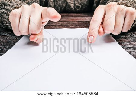 Human hands pointing to up and down points of frame over the blank paper sheet. White copyspace