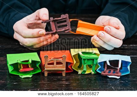 Human hands packing toy furniture to little colorful shopping bags. Concept of handy furniture delivery. Front closeup view
