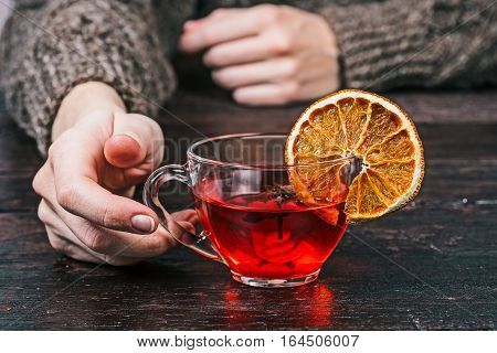 Human hands taking cup of fruit tea. Front view