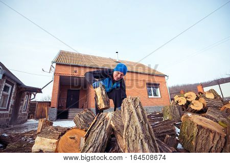 Man With A Strained Face Pulls Out A Log From The Wood Pile