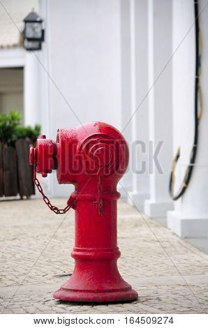 A red fire hydrant on a brick paver sidewalk on the island of Macau China.