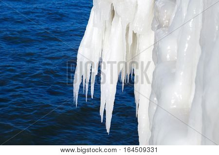 Large icicles on a background of the sea. Ice storm