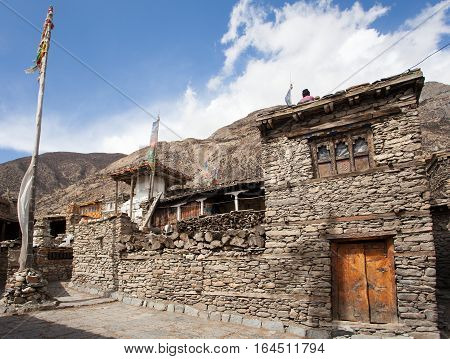 View of local stony building and stupa with prayer flags in Manang village one of the best villages in round Annapurna circuit trekking trail Nepal