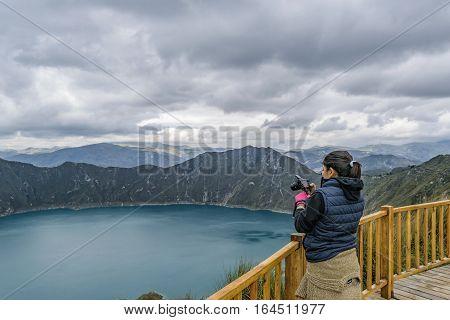 LATACUNGA, ECUADOR, FEBRAURY- 2016 - Young woman taking photo at viewpoint in Quilotoa lake Latacunga Ecuador