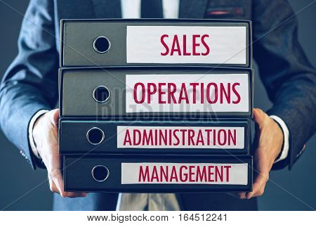 Four core business functions - sales operations administration and management with businessman holding ring binders