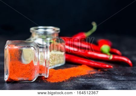 Spices and chili peppers on black table. Paprika powder, oregano and red chili peppers in glass jars on dark wood background