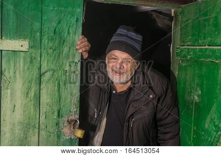 Happy Ukrainian senior peasant looking out from barn