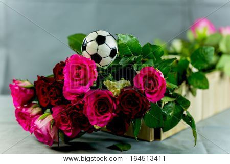 roses with football in a basket, white background