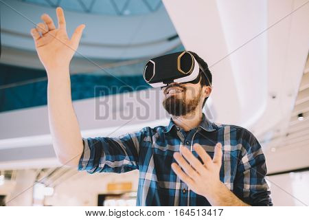 Young man trying vr goggles. Handsome smiling guy is in virtual reality and he is trying to catch something.