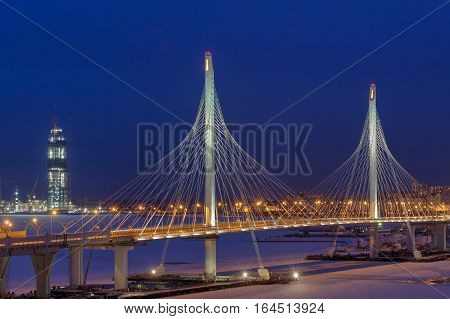 Saint-Petersburg Russia - January 3 2017: A highway crosses frozen river cable bridge at night light in the winter.