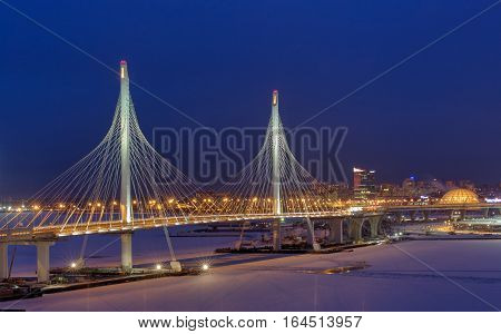 St. Petersburg Russia - January 3 2017: Express roads crosses the river icebound guyed bridge at night lighting in the winter.