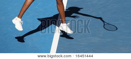 Female tennis player's legs and shadow