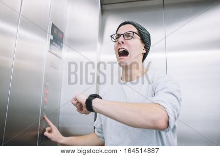 Young stylish guy standing in elevator and sreaming in a despair, because he realised he had missed one of the most important moments in his life. He is crying