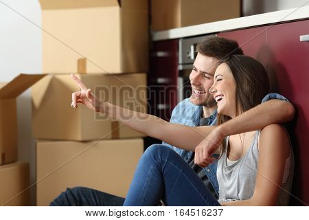 Casual couple sitting on the floor of the kitchen planning relocation of furniture of the house