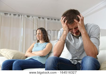 Sad man and his angry girlfriend after argument sitting on a couch at home