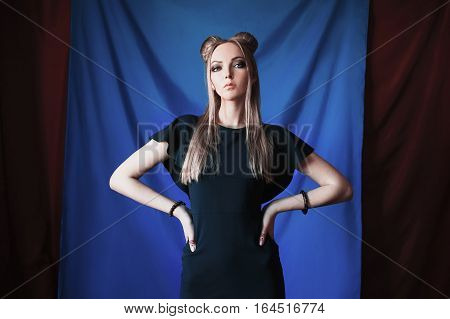 blonde woman with big blue eyes like a elf long white hair in a bun a girl with hairstyle and makeup in a green dress on a blue background looking at the camera