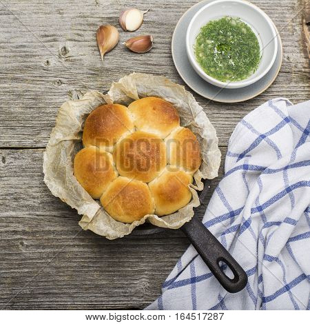 Fresh fragrant baked yeast rolls in the oven with herbs, dill, butter, salt and garlic. Top