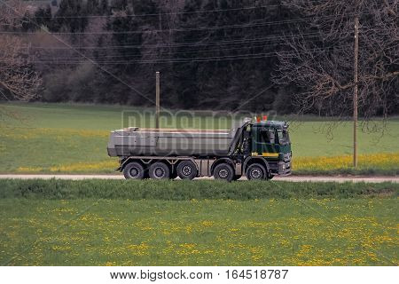 Big truck driving on a road in the summer woods