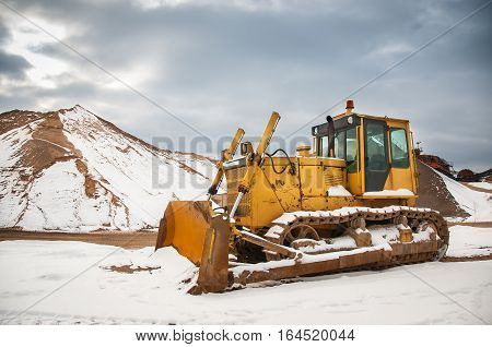Yellow bulldozer in the quarry. Winter and snow.