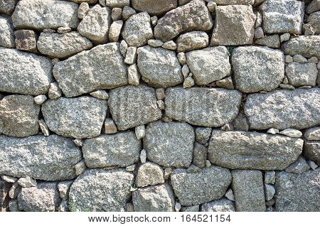 Outdoor stone wall in local stones, stone wall of large boulders, stone wall background