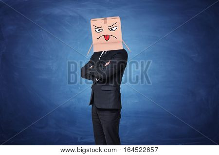 Businessman wearing carton box with painted angry face showing tongue on it on blue blackboard background. Business and communication. Corporate world. Job and personality.