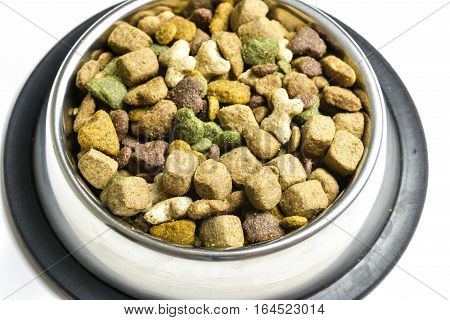 Silver bowl filled with dog-food on a white background.