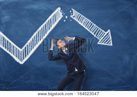 Businessman cowering on blue blackboard background with chalk drawing of white statistic arrow broken in half. Business management. Profit and loss. Business and success.