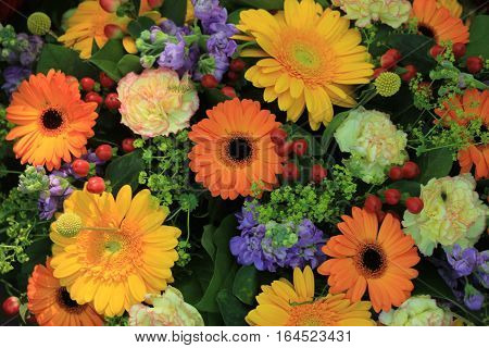 A mixed flower arrangement with yellow and orange gerbers